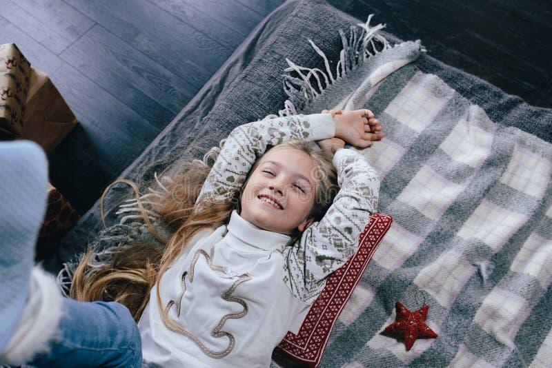 Meisje in een sweater op het bed op een de winterdag Meisje die pret in huis hebben stock foto's