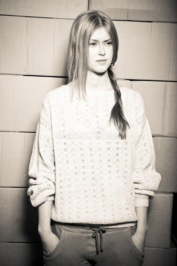 Meisje in een sweater tegen de achtergrond van cardboar stock fotografie