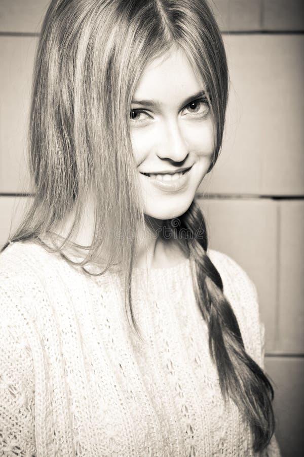 Meisje in een sweater tegen de achtergrond van cardboar stock afbeeldingen