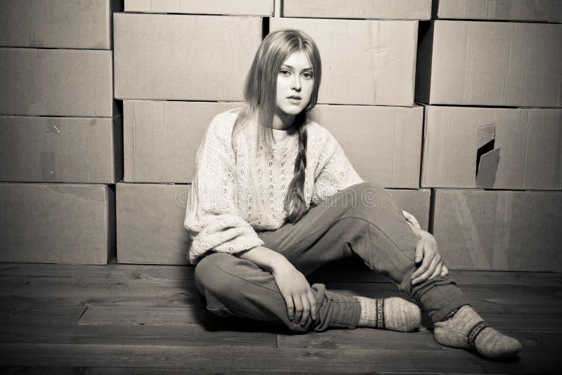 Meisje in een sweater tegen de achtergrond van cardboar stock foto's