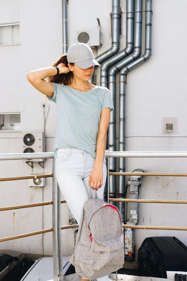 Meisje in een T-shirt, een GLB en jeans stock afbeelding