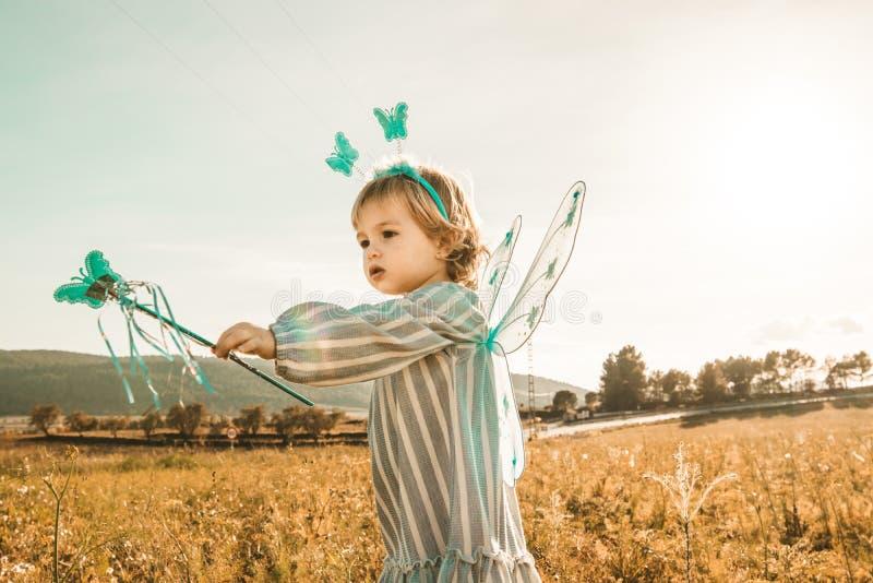 Meisje in een vlinderkostuum met vleugels op het gebied stock afbeelding