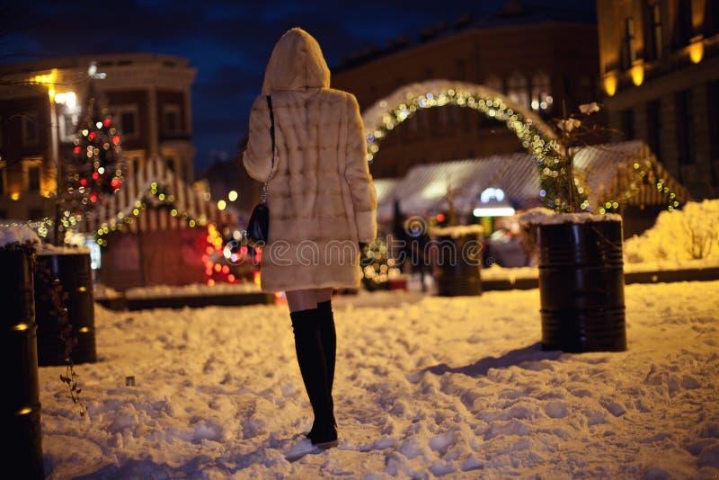 Meisje in een warme bontnertsmantel die in een sneeuwstad lopen royalty-vrije stock foto
