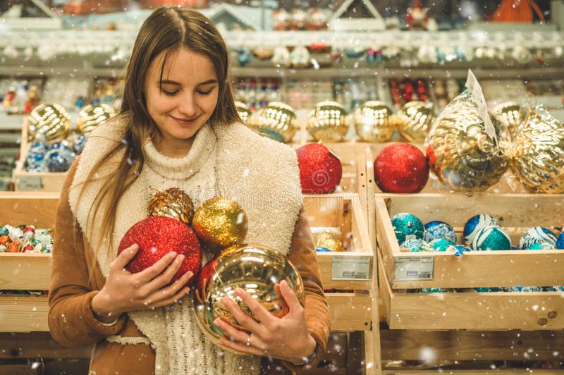 Meisje in een warme laag die grote bal voor Kerstboom in een wandelgalerij houden bij de Kerstmismarkt royalty-vrije stock fotografie