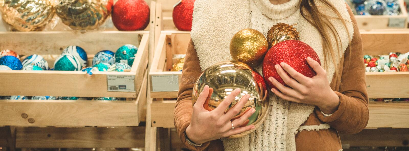 Meisje in een warme laag die grote bal voor Kerstboom in een wandelgalerij houden bij de Kerstmismarkt stock foto's
