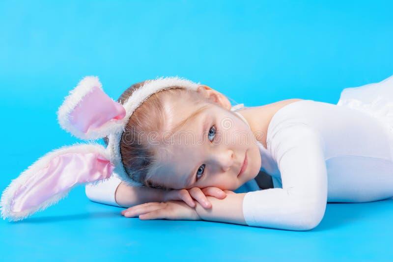 Meisje in een wit konijnkostuum op een blauwe achtergrond De baby ligt dromend op de vloer stock foto
