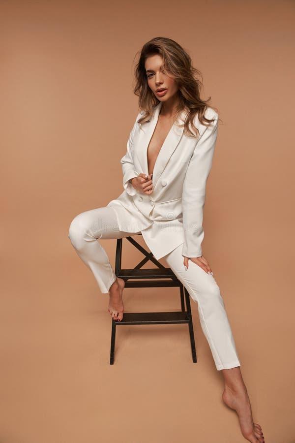 Meisje in een wit pak dat zich op beige achtergrond bevindt royalty-vrije stock afbeelding