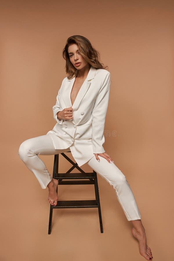 Meisje in een wit pak dat zich op beige achtergrond bevindt royalty-vrije stock fotografie