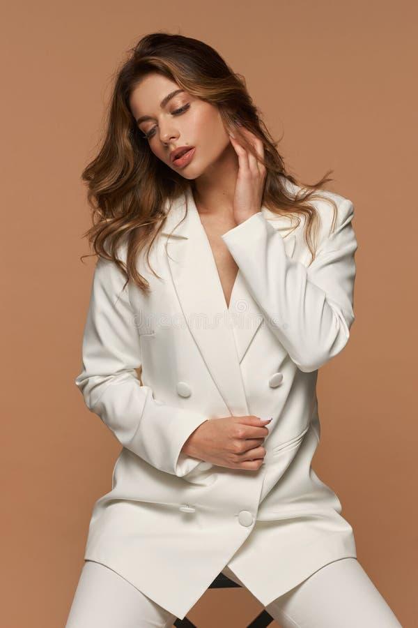 Meisje in een wit pak dat zich op beige achtergrond bevindt stock foto