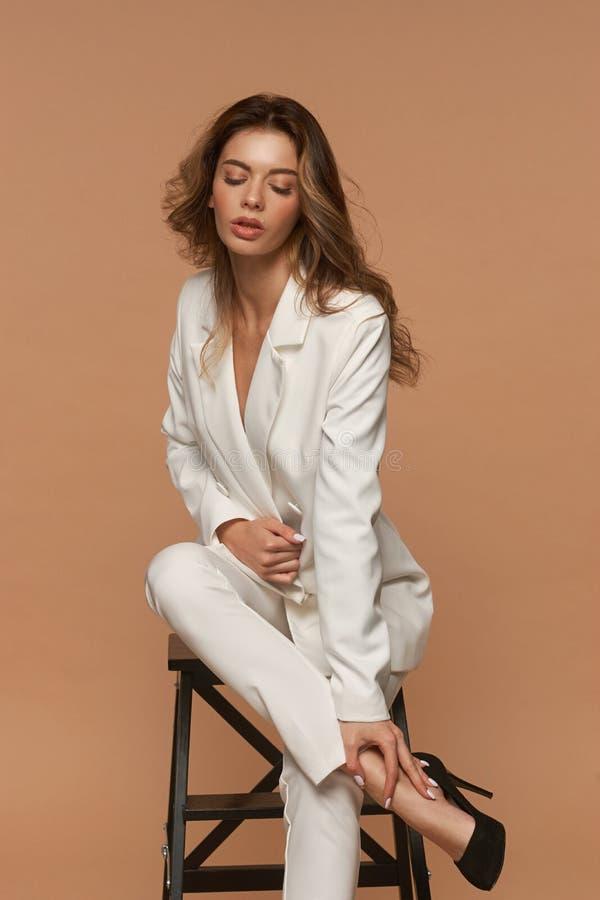Meisje in een wit pak dat zich op beige achtergrond bevindt stock afbeeldingen