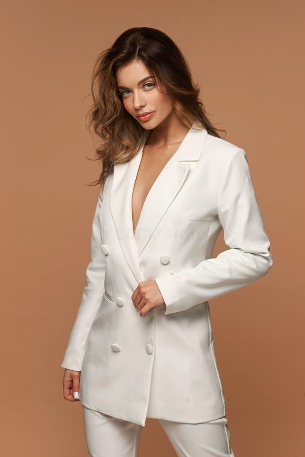 Meisje in een wit pak dat zich op beige achtergrond bevindt stock afbeelding