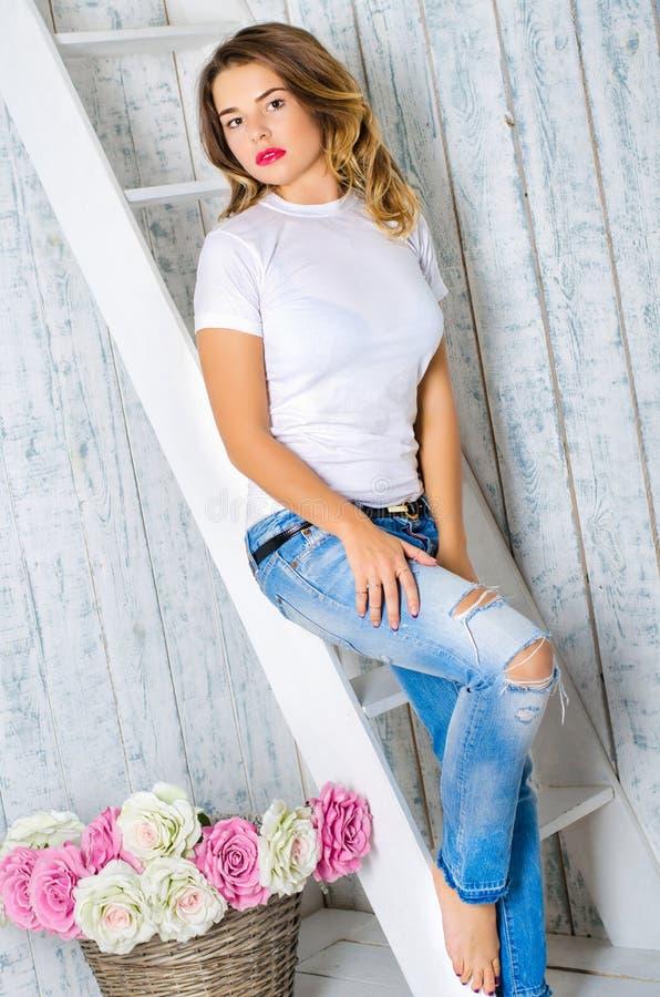 Meisje in een witte T-shirt en jeans stock foto's