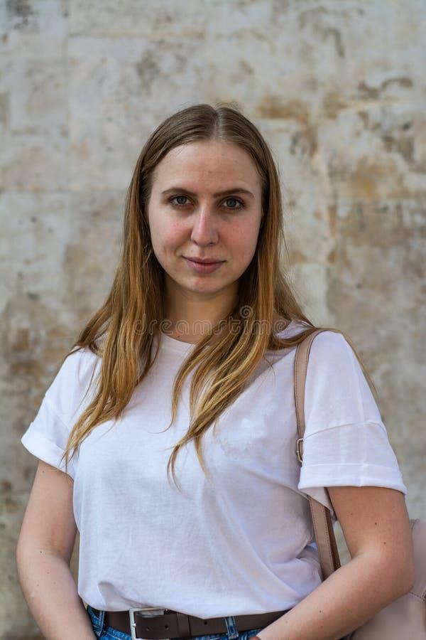 Meisje in een witte T-shirt en jeans op de achtergrond van de oude muur in de stad stock fotografie