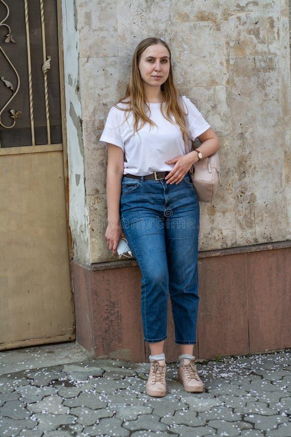 Meisje in een witte T-shirt en jeans op de achtergrond van de oude muur in de stad royalty-vrije stock foto