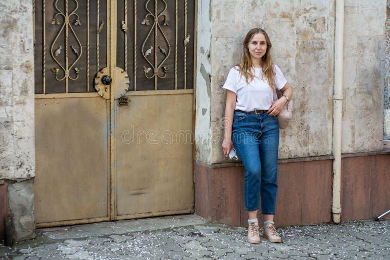 Meisje in een witte T-shirt en jeans op de achtergrond van de oude muur in de stad royalty-vrije stock afbeeldingen