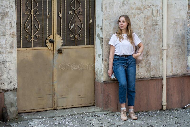 Meisje in een witte T-shirt en jeans op de achtergrond van de oude muur in de stad stock foto
