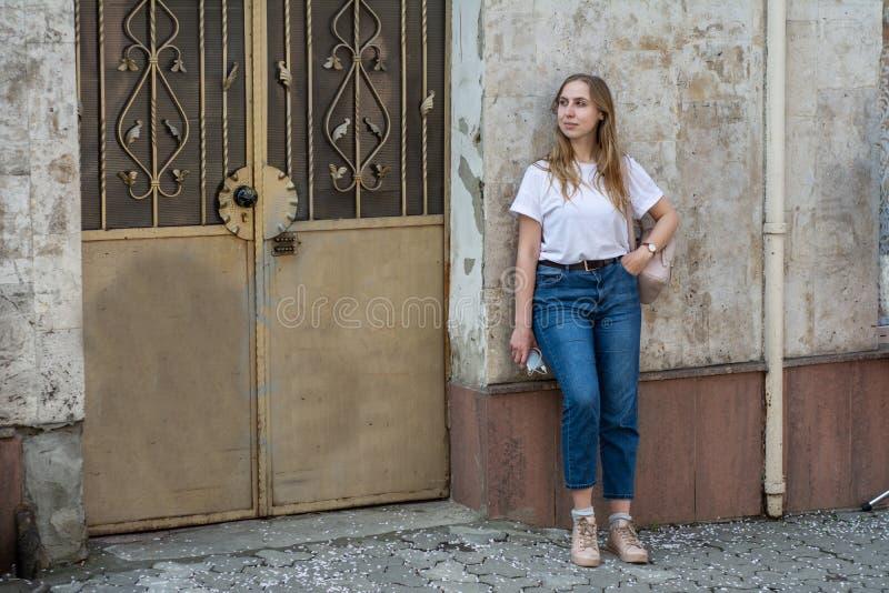 Meisje in een witte T-shirt en jeans op de achtergrond van de oude muur in de stad stock afbeelding
