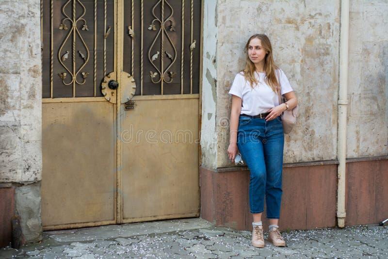 Meisje in een witte T-shirt en jeans op de achtergrond van de oude muur in de stad royalty-vrije stock fotografie