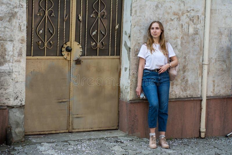 Meisje in een witte T-shirt en jeans op de achtergrond van de oude muur in de stad stock foto's