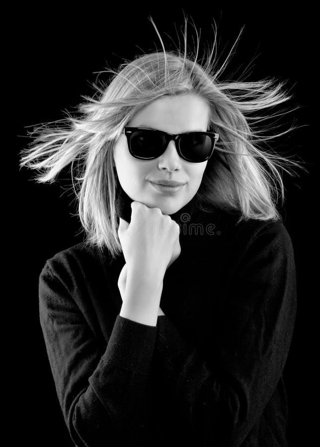 Meisje in een zwarte col met retro zonnebril stock foto