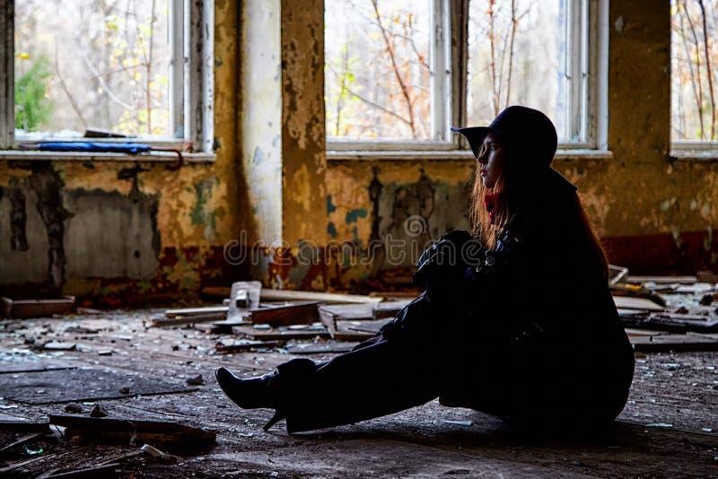 Meisje in een zwarte mantel en hoedenzitting in een geruïneerde ruimte Fotospruit in een ongebruikelijke plaats stock fotografie