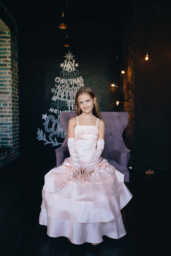 Meisje in elegante kledingszitting als voorzitter op de achtergrond van Kerstmisdecoratie royalty-vrije stock fotografie