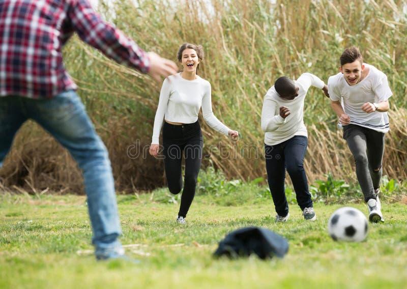 Meisje en drie jongens die voetbal in de lente park en het glimlachen spelen royalty-vrije stock foto