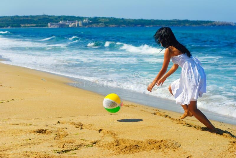 Meisje en een bal op het strand stock fotografie