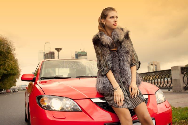 Meisje en een rode auto stock afbeeldingen