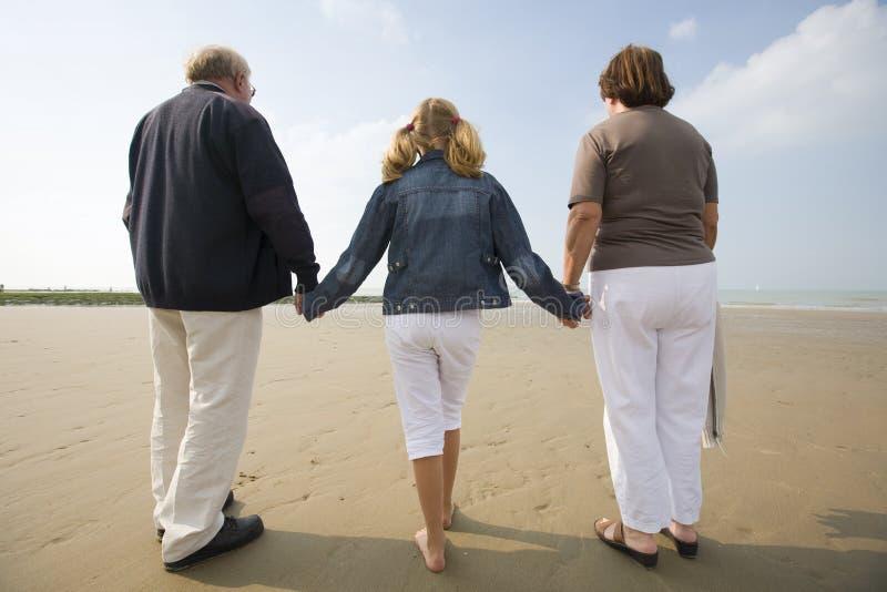 Meisje en grootouders die bij het strand lopen stock foto's