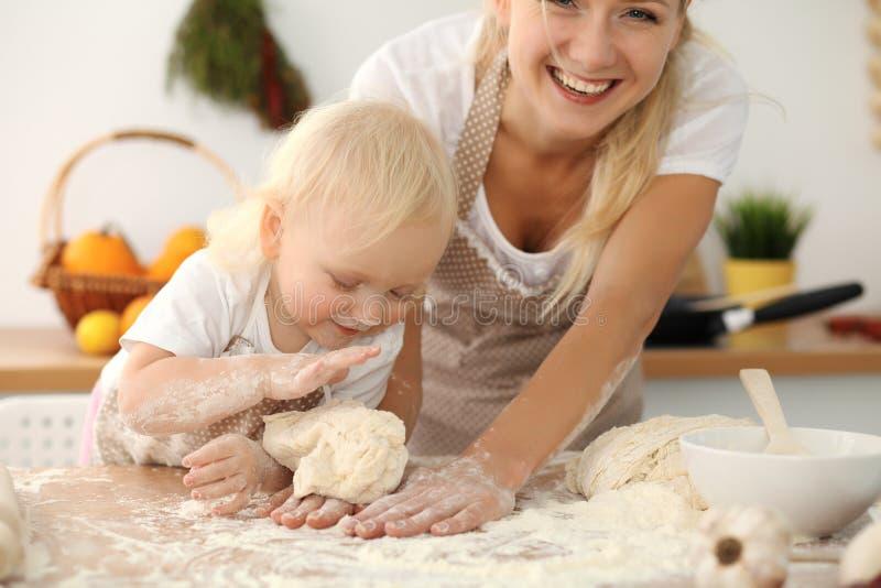 Meisje en haar blondemamma in beige en schorten die terwijl het kneden van het deeg in keuken spelen lachen Eigengemaakt gebakje stock foto