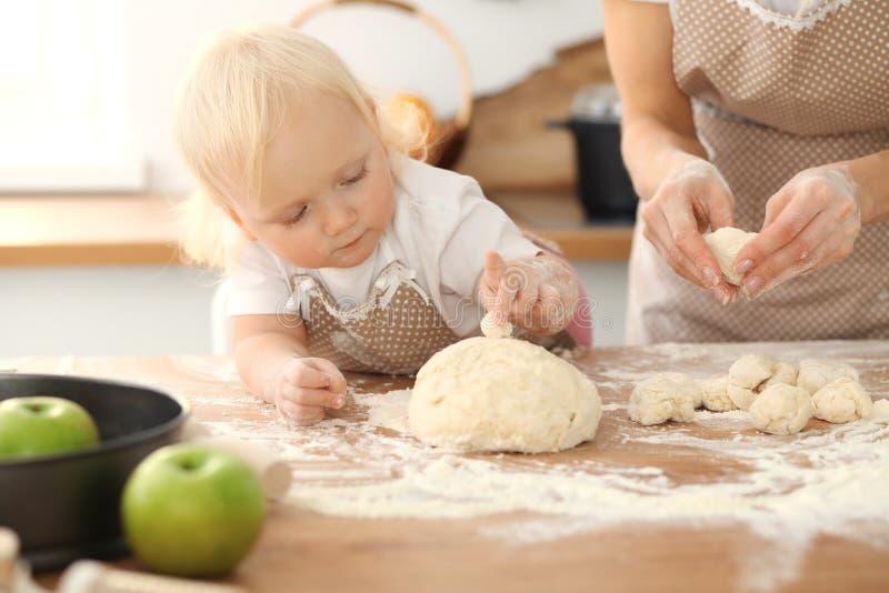 Meisje en haar blondemamma in beige en schorten die terwijl het kneden van het deeg in keuken spelen lachen Eigengemaakt gebakje royalty-vrije stock foto