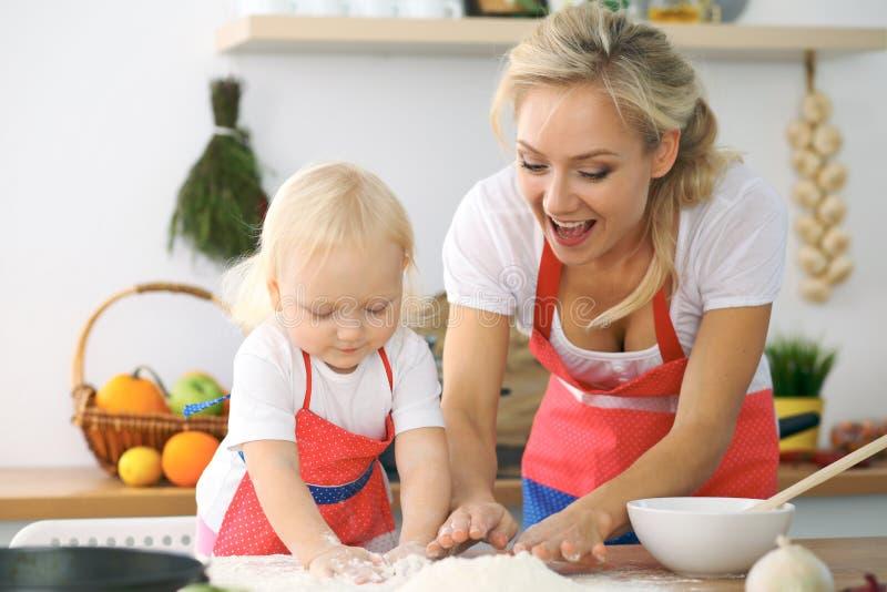 Meisje en haar blondemamma in rode en schorten die terwijl het kneden van het deeg in de keuken spelen lachen Homemad royalty-vrije stock afbeeldingen