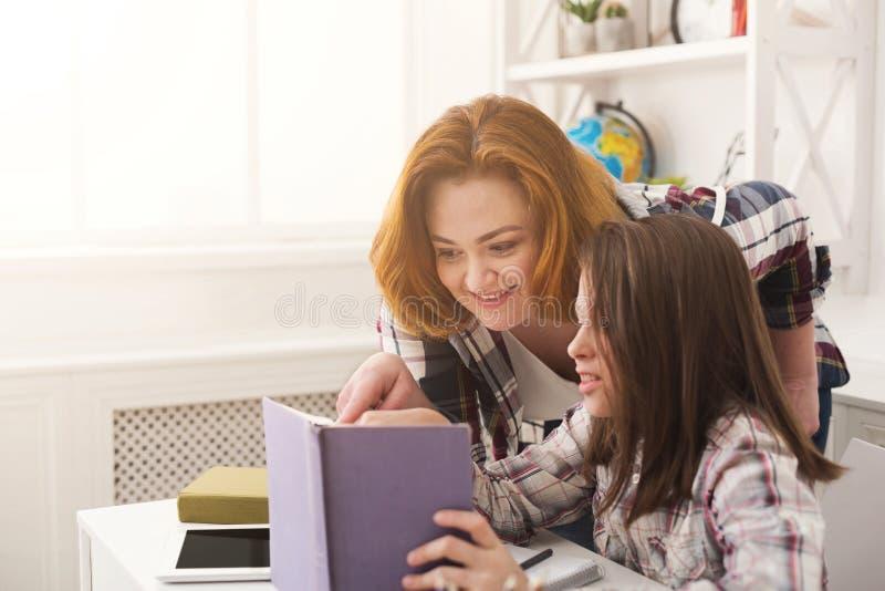 Meisje en haar boek van de mammalezing thuis stock afbeeldingen
