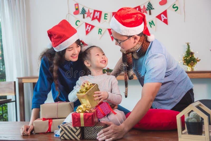 Meisje en haar de giftdozen van ouders open Kerstmis stock afbeeldingen