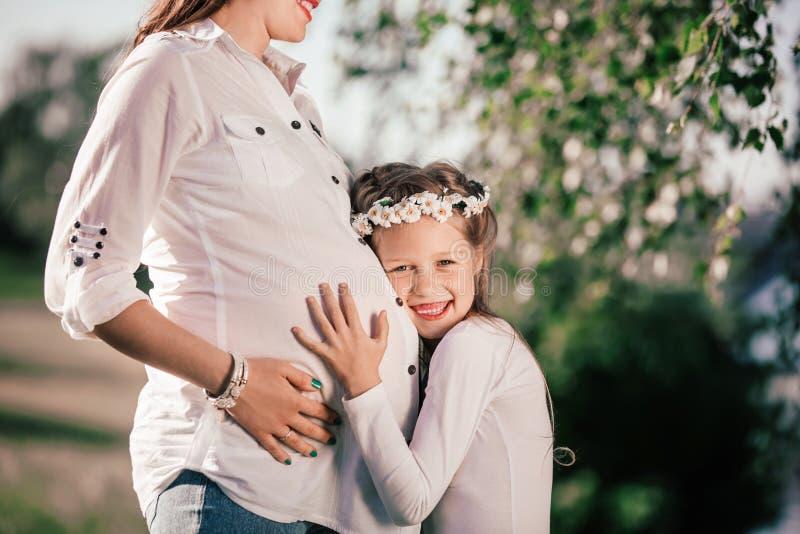 Meisje en haar gelukkig zwanger mamma op een gang in het de zomerpark royalty-vrije stock afbeeldingen
