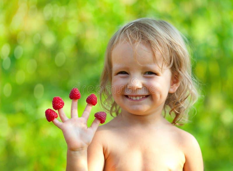 Meisje en haar hand met framboos stock fotografie