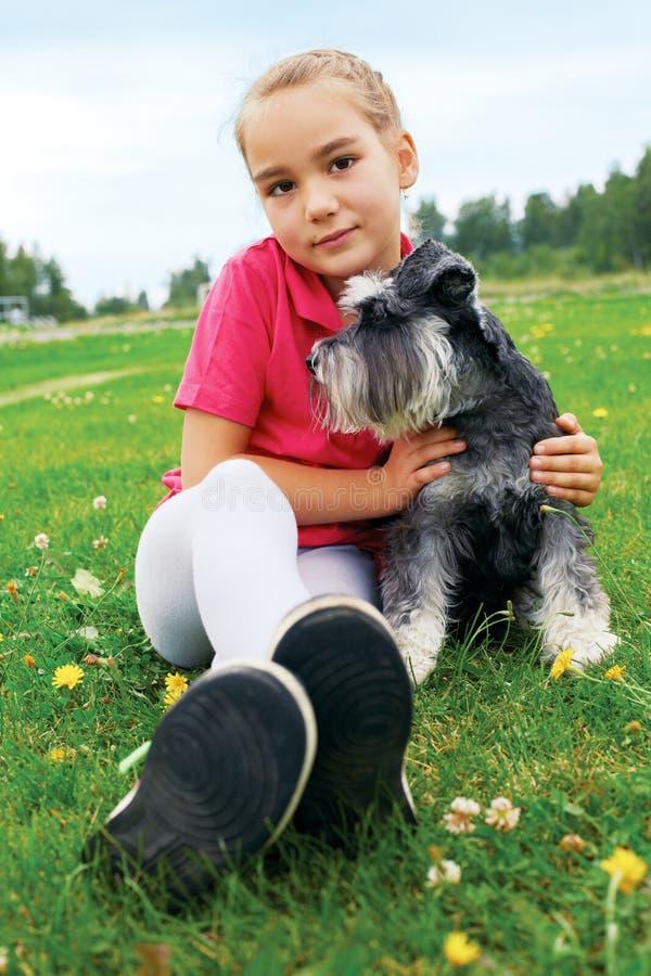 Meisje en haar hond die op het gras in het park op een de zomerdag liggen stock afbeeldingen