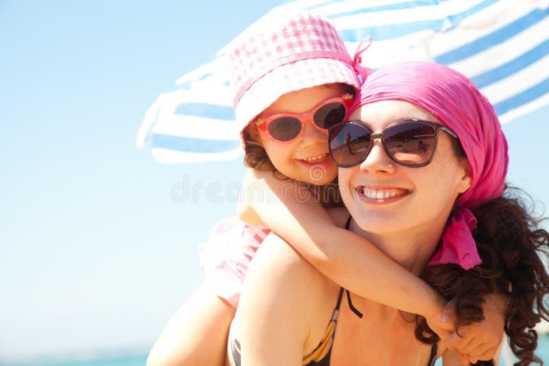 Meisje en haar moeder bij de kust stock fotografie