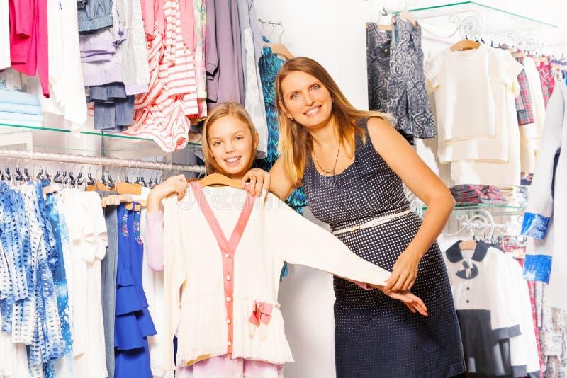 Meisje en haar moeder die de witte sweater houden stock foto's