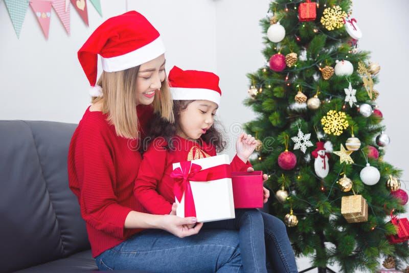Meisje en haar moeder die santahoed dragen terwijl thuis het openen van Kerstmisgift stock afbeelding