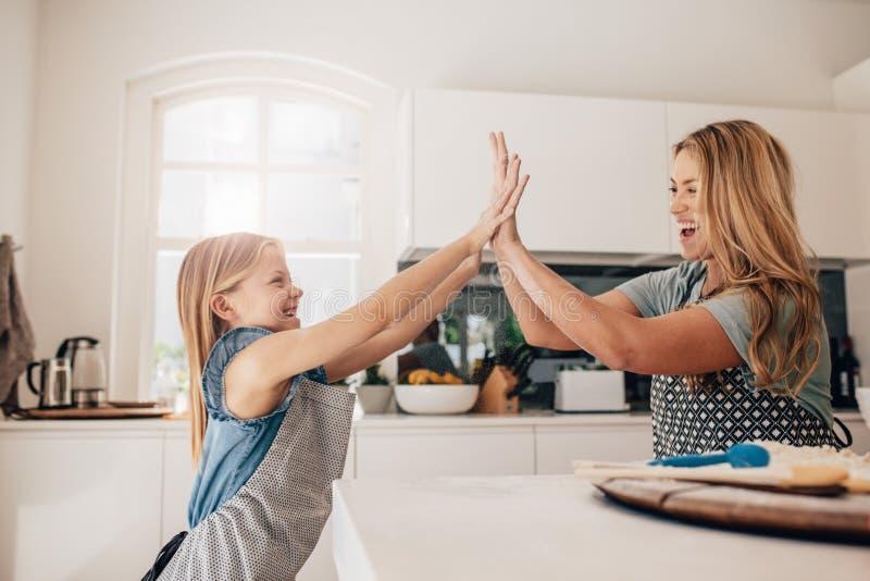 Meisje en haar moeder in keuken die hoogte vijf geven royalty-vrije stock foto