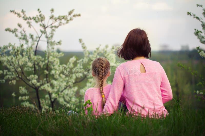 Meisje en haar moederzitting op gras in de zomerdag Mening van een rug royalty-vrije stock afbeeldingen