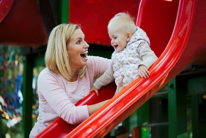 Meisje en haar mooie jonge moeder die op de speelplaats spelen royalty-vrije stock fotografie