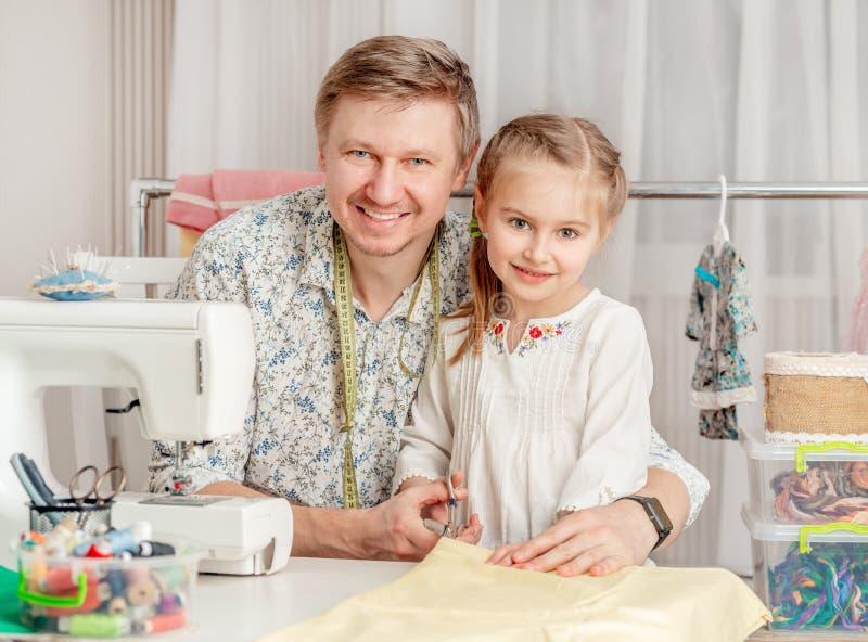 Meisje en haar papa in een naaiende workshop royalty-vrije stock afbeeldingen