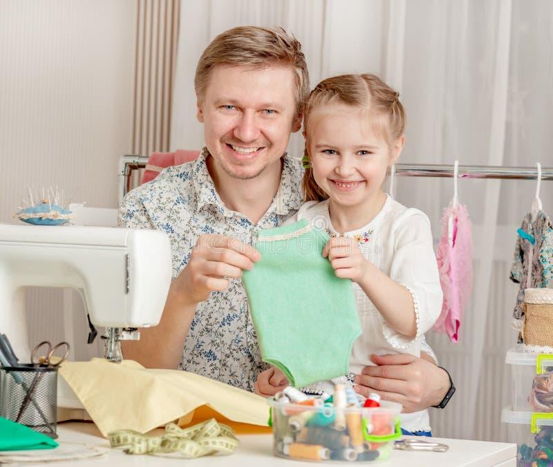 Meisje en haar papa in een naaiende workshop stock afbeeldingen