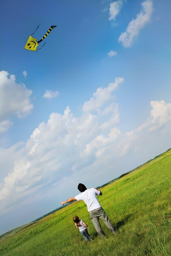 Meisje en haar vader met het vliegen van een vlieger royalty-vrije stock foto's