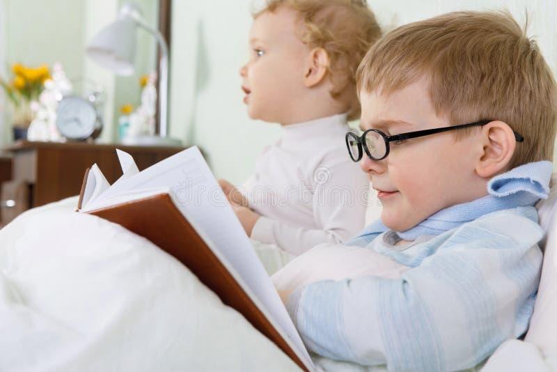 Meisje en haar zieke broer die in bed liggen royalty-vrije stock afbeelding