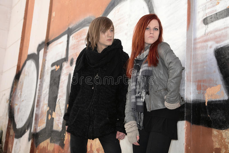 Meisje en jonge mens tegen muur van graffiti stock foto's
