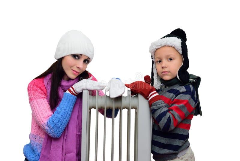 Meisje en jongen dichtbij een verwarmde radiator royalty-vrije stock afbeeldingen